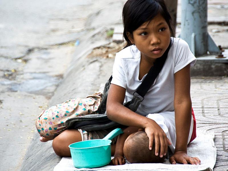 道端で幼い赤ちゃんと一緒に物乞いをする少女